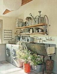 That sink, the gray wainscoting, those watering cans, the plants!