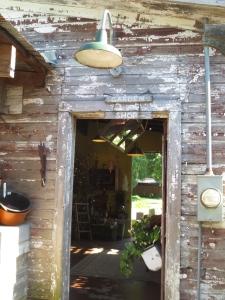 I'm loving the chippy white wood + the old gooseneck light fixture!
