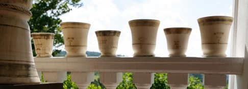 guy wolff white pots on a porch rail