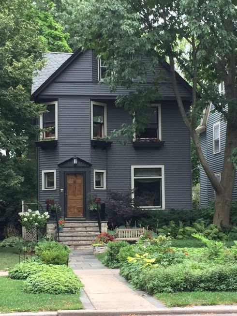 cape cod of black victorian with busy front yard