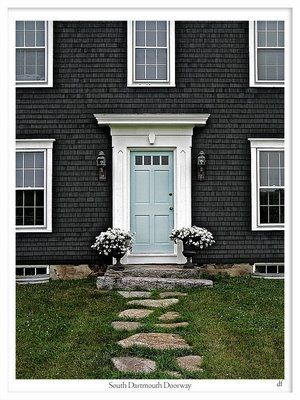 cape cod of black with blue door